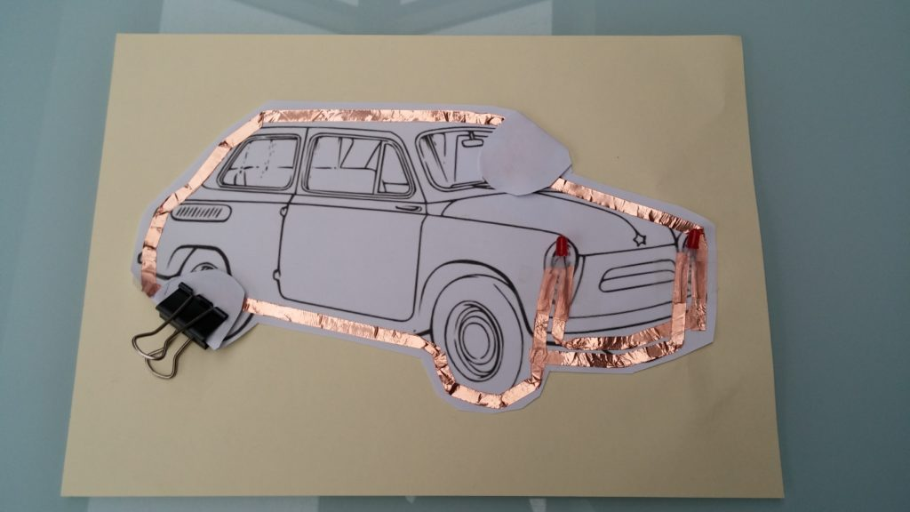Car on paper with bronze conductive tape around it.